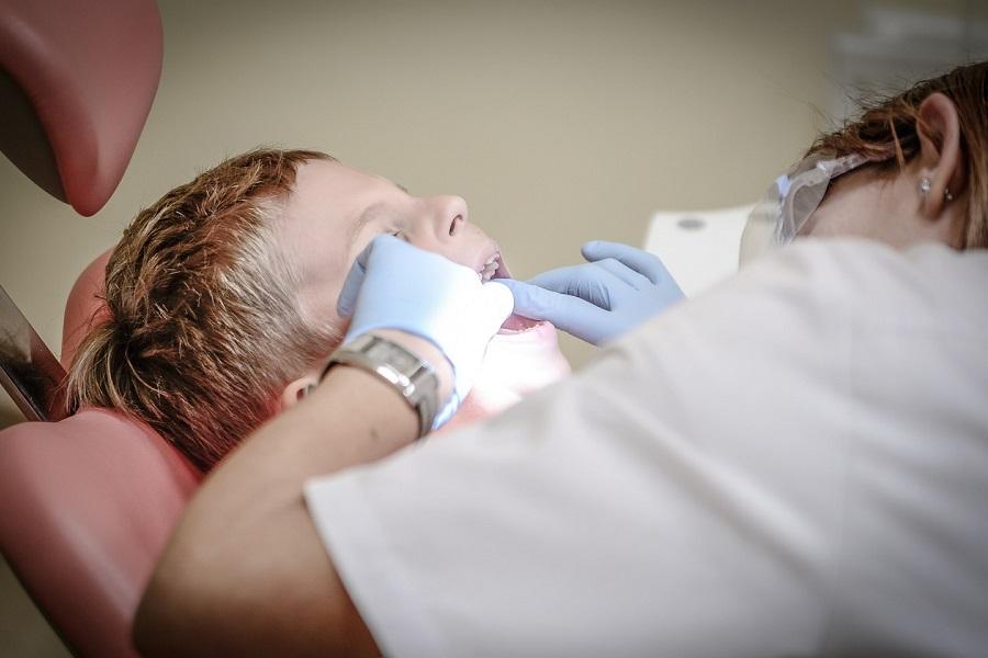 Zahnärtzin untersucht Zähne eines Kindes